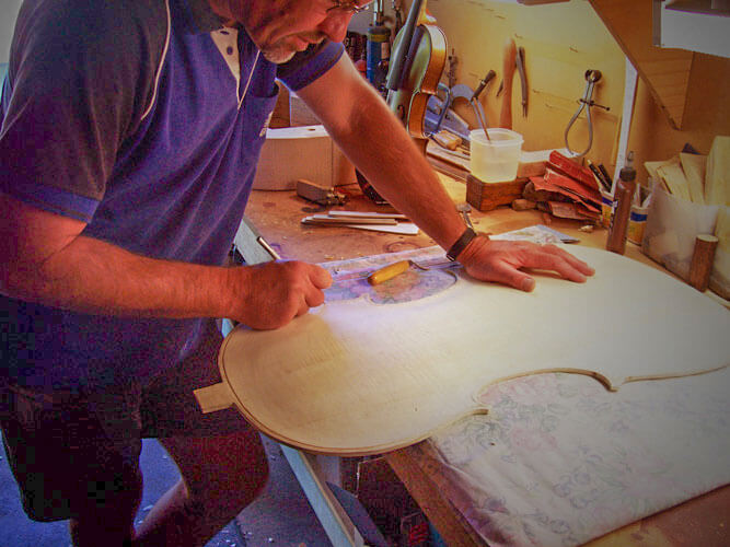 Peter Reid luthier carving the wood