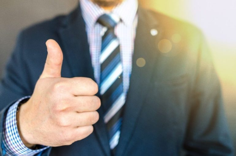 man in a suit gives a thumbs up