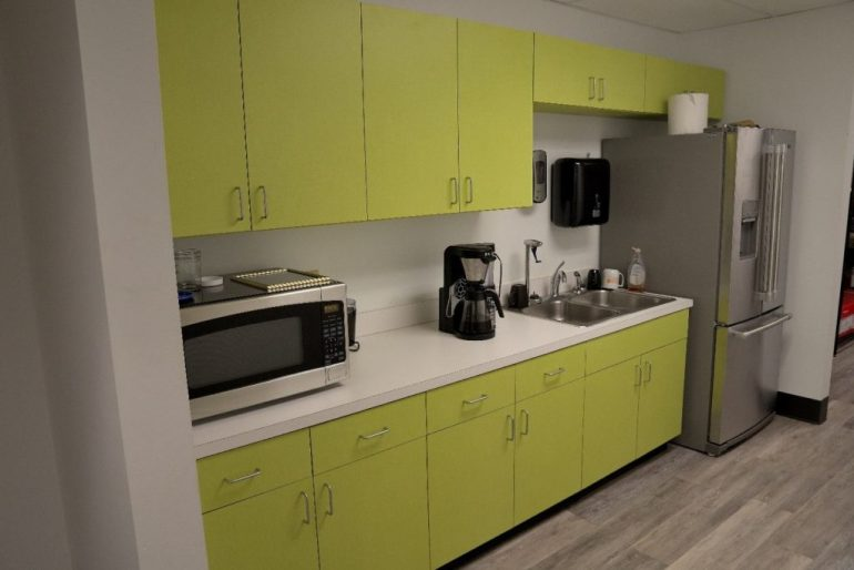 a kitchenette with coffeemaker, microwave and refrigerator