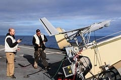 Men perform pre-flight checks on an unmanned a...