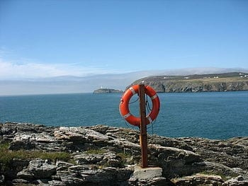 English: Life buoy post on rocky promontory on the north side of Porth y Gwin The camera point north-westerly across Abraham's Bosom and towards the South Stack Lighthouse. A fog bank, soon to envelope the whole of Holy Island, can be seen approaching from the Irish Sea. (Photo credit: Wikipedia)