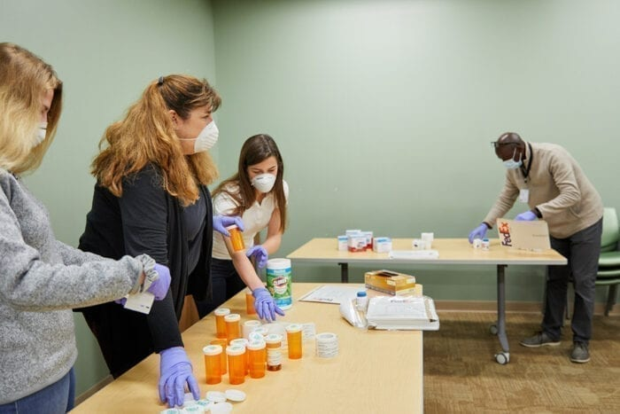 Julia Schweiger (black shirt), lab manager in Eric Lenze's lab, organizes packets for a COVID-19 trial with the help of professional rater Leonard Imbula, and her daughters, research coordinator Abigail Schweiger (white shirt) and Nadia Schweiger (grey shirt) at the Taylor Avenue Building on April 9, 2020. MATT MILLER/WASHINGTON UNIVERSITY SCHOOL OF MEDICINE