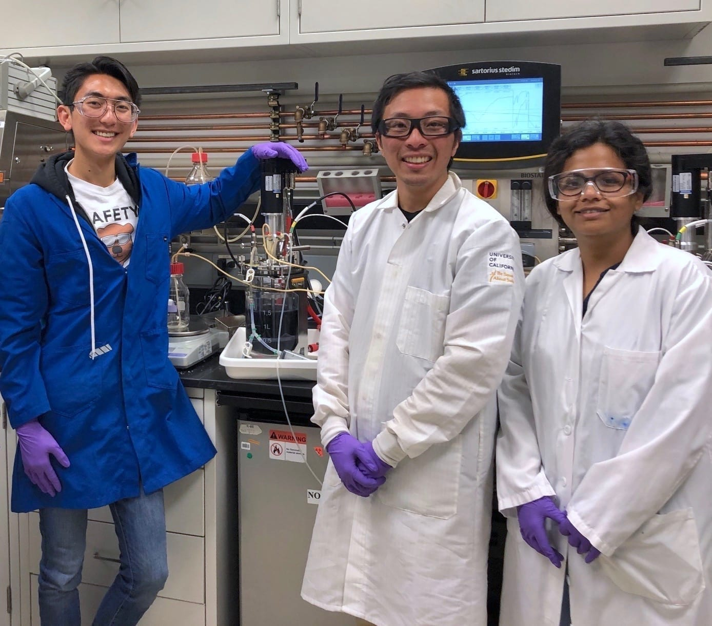 Study authors (from left to right) Andrew K. Lau, Thomas Eng, and Deepanwita Banerjee stand in front of a two-liter bioreactor containing P. putida cells that are producing indigoidine, which causes the strong dark blue color of the liquid. This photo was taken at JBEI in July 2019. (Credit: Berkeley Lab)