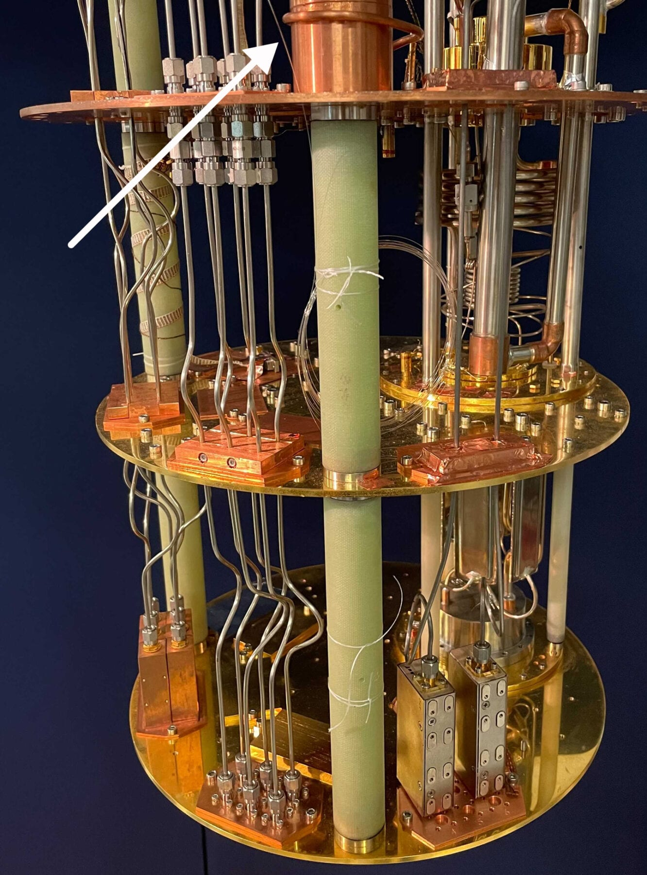 NIST physicists measured and controlled a superconducting quantum bit (qubit) using light-conducting fiber (indicated by white arrow) instead of metal electrical cables like the 14 shown here inside a cryostat. By using fiber, researchers could potentially pack a million qubits into a quantum computer rather than just a few thousand. Credit: F. Lecocq/NIST