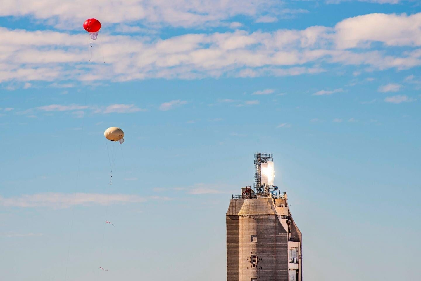 SPOTLIT BY SUN POWER — A multidisciplinary team of researchers from Sandia recently used tethered balloons to collect samples of airborne dust particles to ensure the safety of a falling-particle receiver for concentrating solar power.