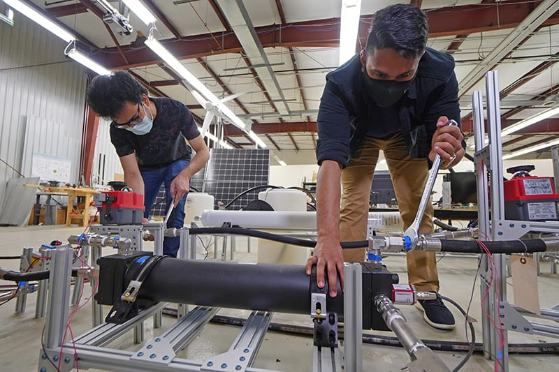 """Graduate students Abhimanyu Das (left) and Akshay Rao adjust a piston tank, the key component to a new desalination process called """"double-acting batch reverse osmosis."""" (Purdue University photo/Jared Pike)"""