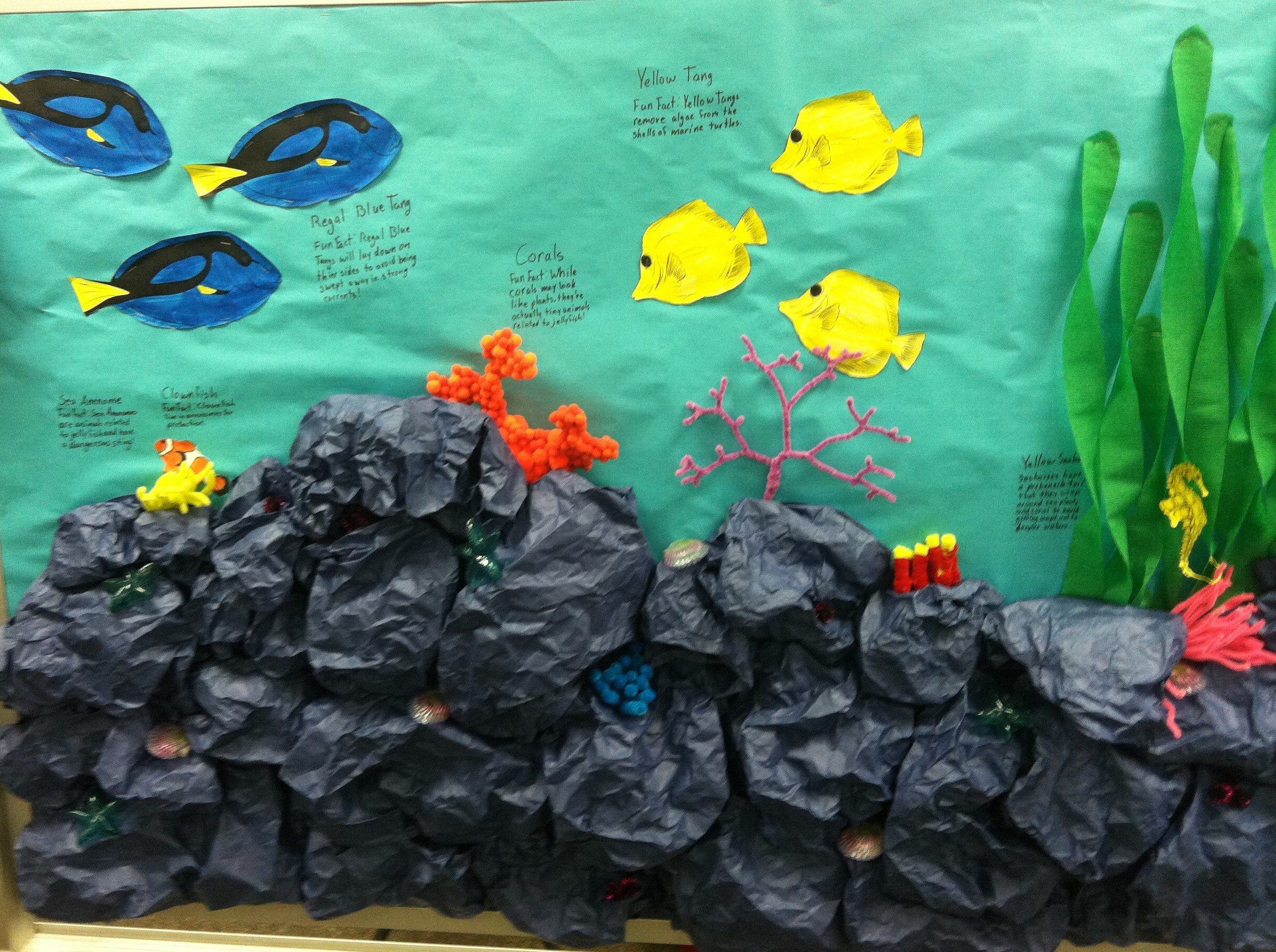 This isn't difficult to create at all. The coral is made of black paper that has been crumpled together. In fact, you can even use old paper from previous projects to create these looks. The seaweed is just a green streamer. The three dimensions of the coral really make it pop out. Teachers and students will really enjoy what you have made.