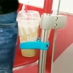 L'adaptateur Comfy Cup se présente sous la forme d'une pince qui se fixe sur un tube largement répandu dans les transports en commun.