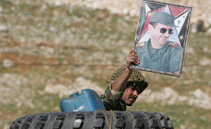 Сирийский солдат с плакатом президента Башара Аль-Асада