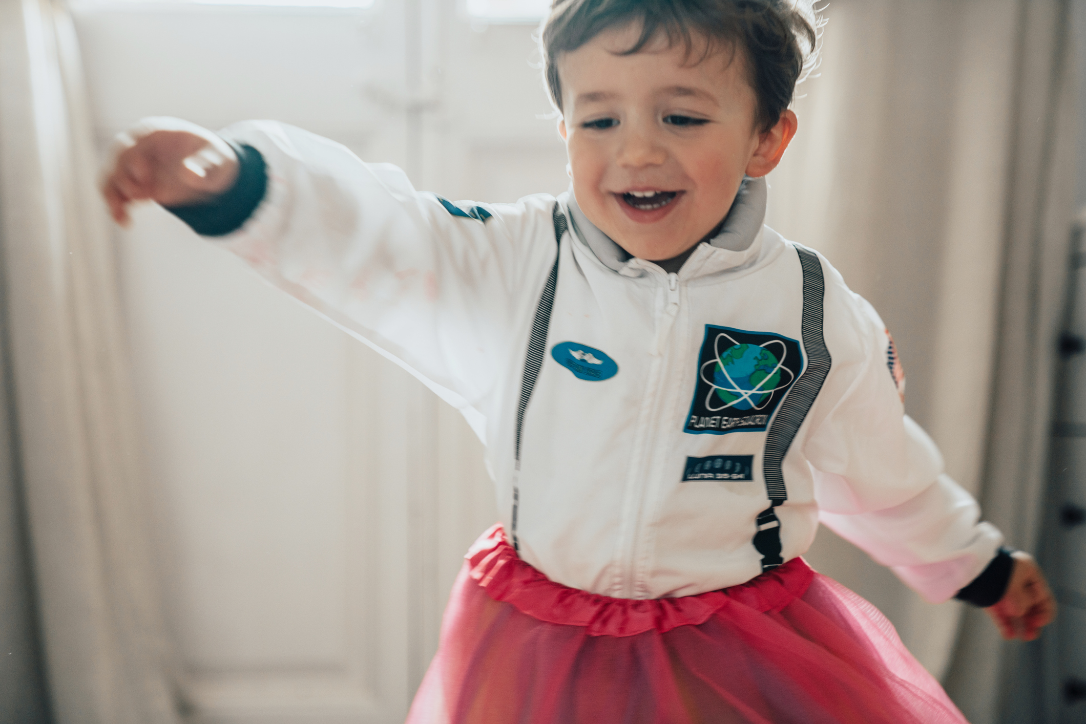 white child with short brown hair dancing in an astronaut costume and a pink tutu