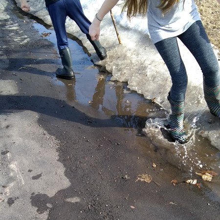 Two kids splashing in a puddle
