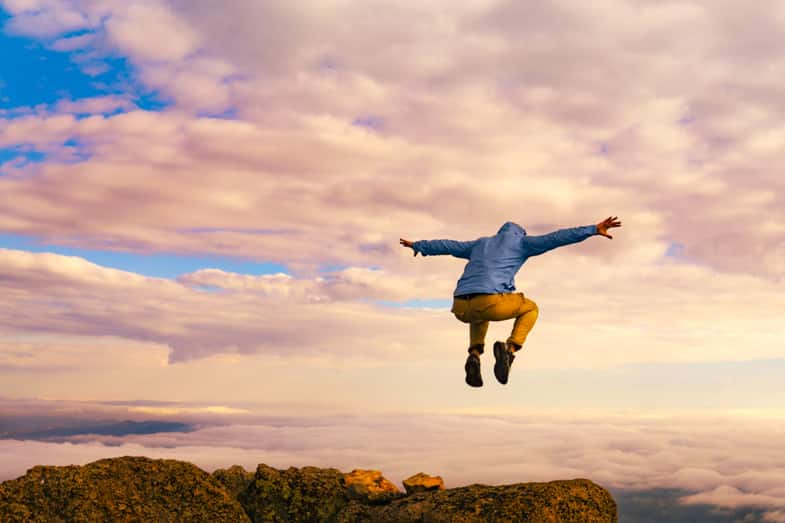 man showing self-belief by jumping over a cliff