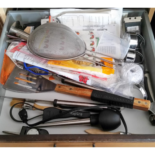 A messy kitchen drawer before it was decluttered. Using these 6 decluttering tips will help you clear out the clutter.