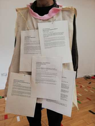 A person stands wearing a beige tabard. There are printed documents clipped to the front of the garment.