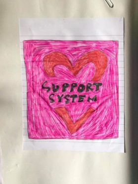 A lined piece of paper with a red heart drawn inside a pink square. There is some black text reading 'support system'
