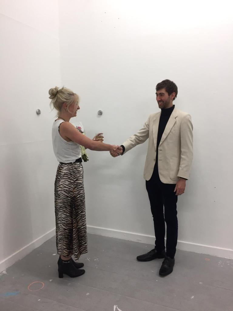 Two people standing against a white wall shake hands. They are both smiling.
