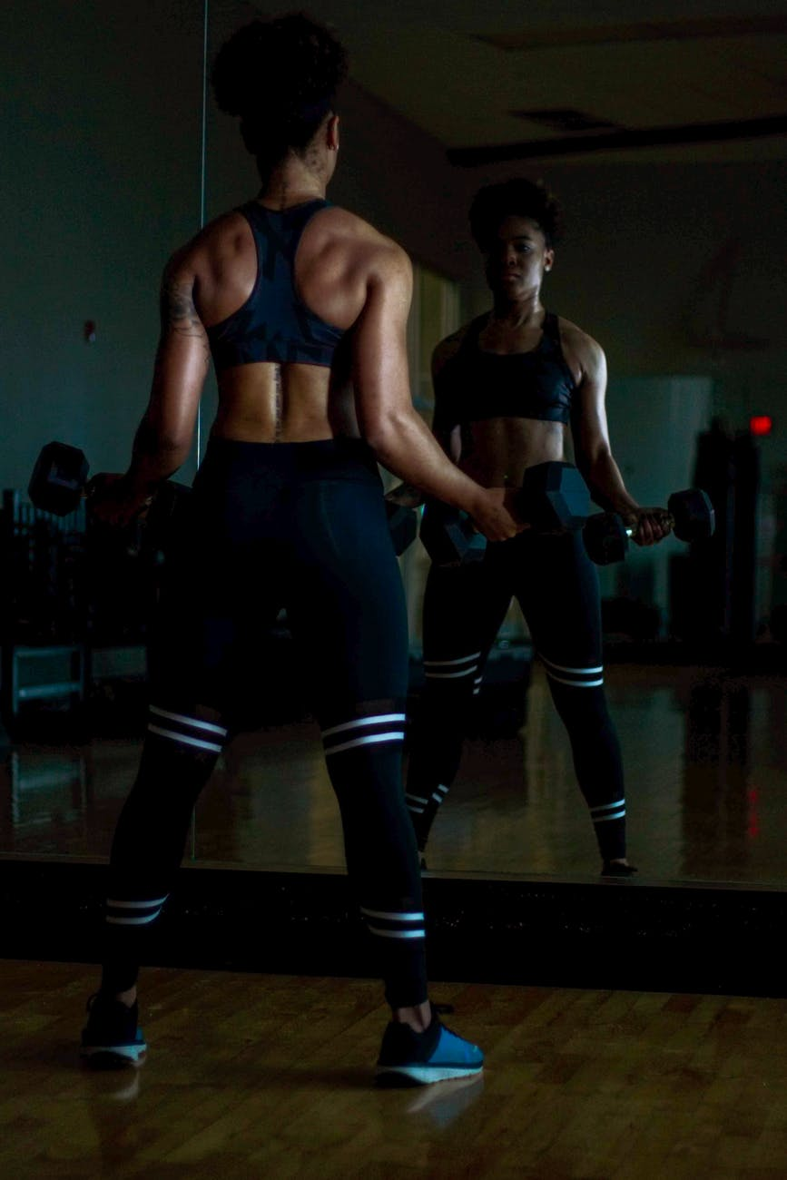 woman lifting two dumbells on both hands in front of mirror