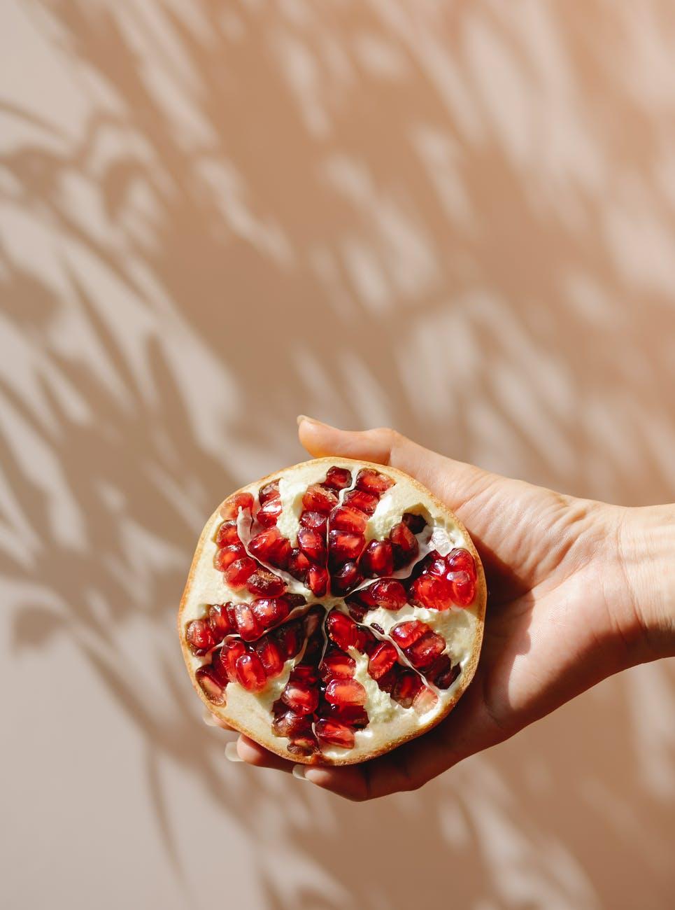 crop woman demonstrating ripe pomegranate