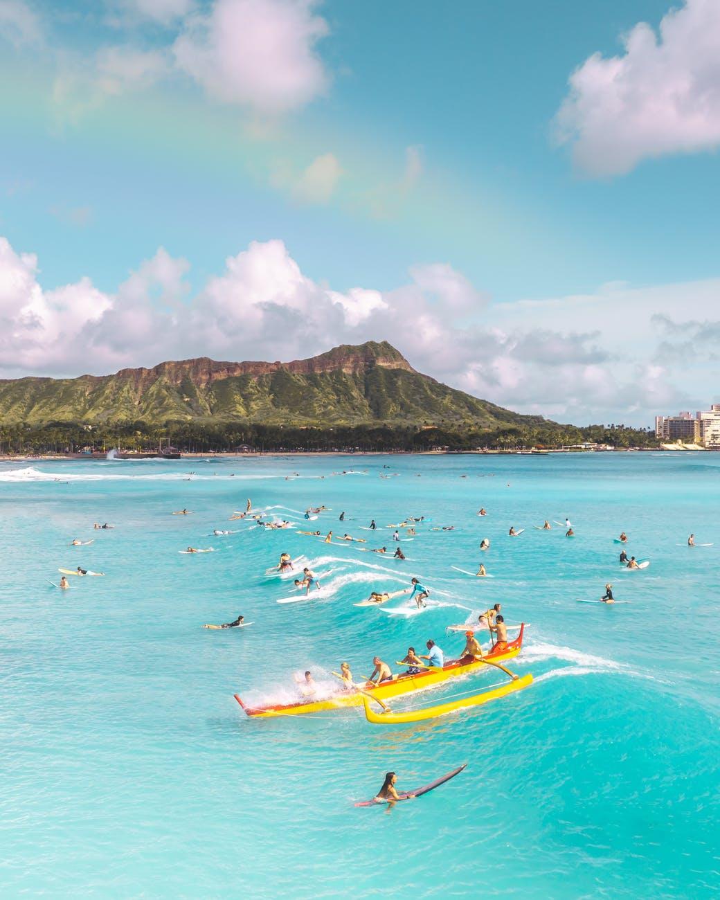 people riding yellow kayak on sea