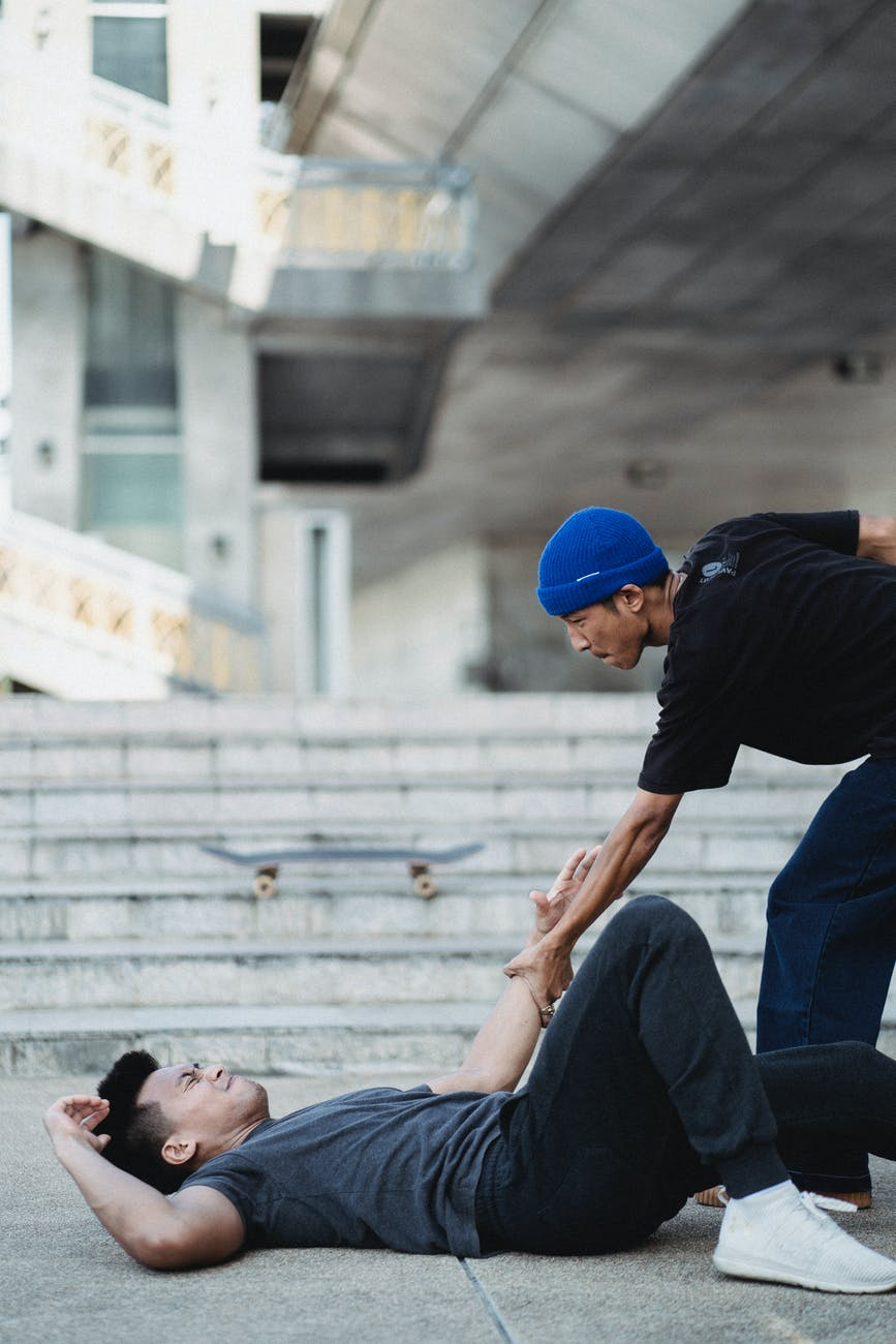 asian man helping friend while meeting on street