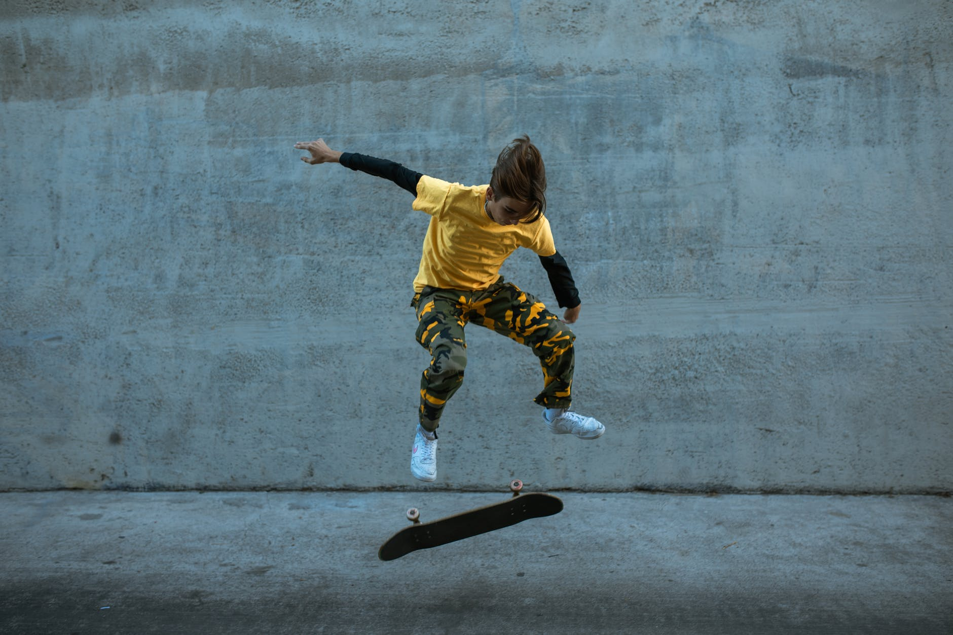person in yellow shirt jumping on the skateboard