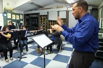 Teacher conducting students in music class.