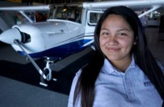 High school female student smiling in front of airplane.