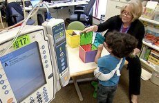 Young student playing with a colorful box at the Lucile Packard Children's Hospital Stanford with teacher.