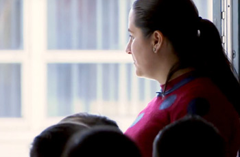 Teacher looking out of classroom door with students standing nearby.