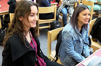 Students sitting down at table, smiling