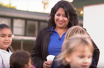 School principal, Roxanna Villasenor talking with students on playground.