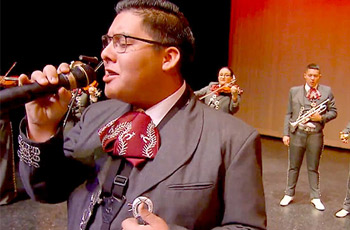 male mariachi student dressed in costume, singing in band.