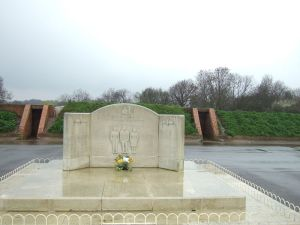 The war memorial at Kenley, with the old blast shelters in the background