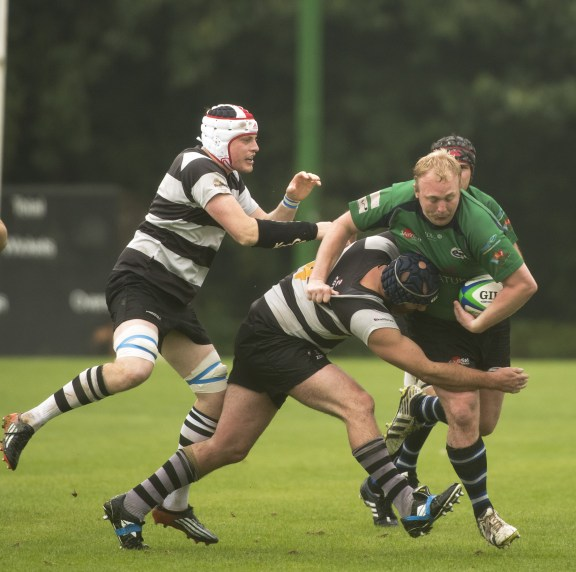 Forcing a break-out: Old Mid-Whitgiftians' Nathan Bacon, in green, battles against the Farnham defence. Photo by Peter Filewood