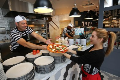 Pizzaiolo Jorge Salvador passing the first pizza baked at PizzaExpress Coulsdon to waitress Eleni Lepida