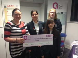 Pupils at Quest handover a charity cheque from First Give
