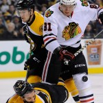 Boston Bruins center Chris Kelly (23) takes a hit from Chicago Blackhawks right wing Marian Hossa (81) in front of the goal.