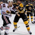 Boston Bruins center Chris Kelly (23) and Chicago Blackhawks center Andrew Shaw (65) fight during the third period.