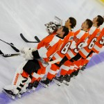Members of the Philadelphia Flyers lineup on the blue line during the national anthem