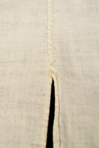 The seam along the back of the waistcoat is sturdy although not as neat as the more visible seams, such as those along the bottom and front edges.