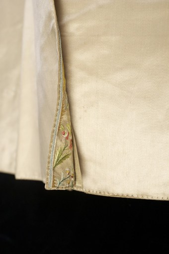The embroidery along the tails continues into the folds.