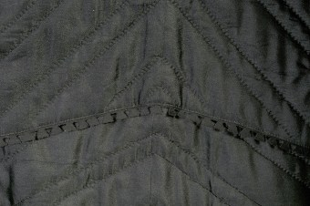 The felted finish of the wool prevented it from unraveling. The bottom edge of the coat is actually the raw edge of the fabric. The raw edges of the facings on the interior however, are finished with a pinked edge, which resembles dovetail joints.