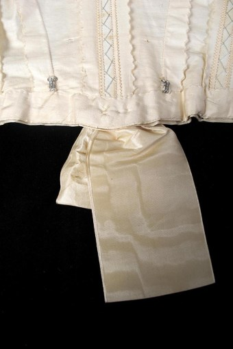 The waist of the bodice has two hooks at the center back, which align with corresponding eyes on the skirt's waistband. These points of attachment ensured that the dress remained straight and in place.