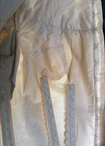 The loose front of the bodice also conceals a secret pocket in the underbodice. The pocket is not visible when the dress is worn, but its outline can be seen in this backlit photo. Most likely the bride tucked a personal keepsake next to her heart.