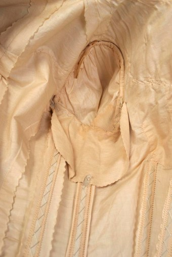 The dress includes shields in the armpits to protect the silk from staining and discoloration.