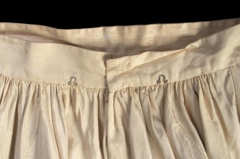 The waist of the skirt has two eyes at the center back, which align with corresponding hooks on the inside of the bodice. These points of attachment ensured that the dress remained straight and in place.