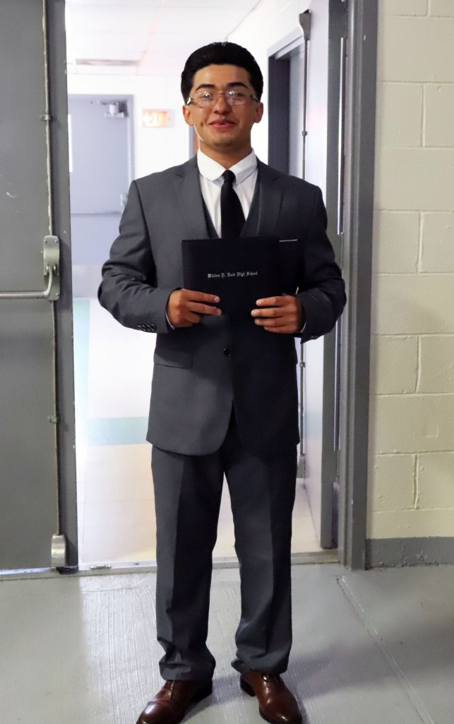 student in suit after ceremony