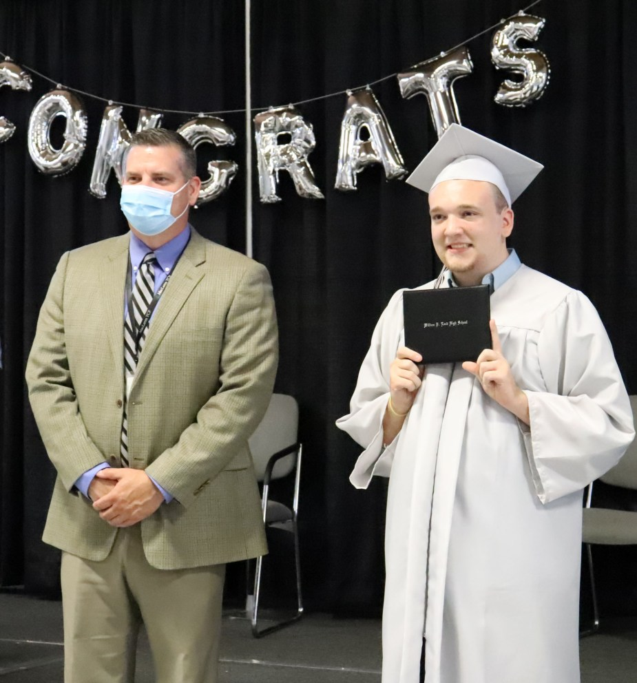student in cap and gown with superintendent