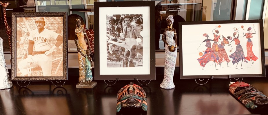 framed photos and artwork depicting Africans and African Americans, sitting on a table