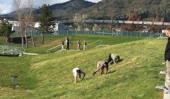 three teen boys crawl across a grassy field